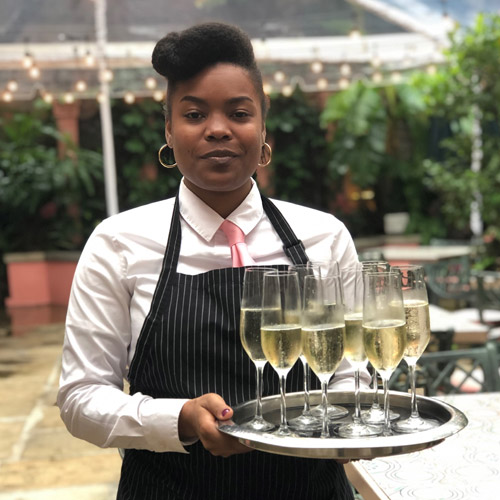 Waitress with tray of wine glasses in the courtyard