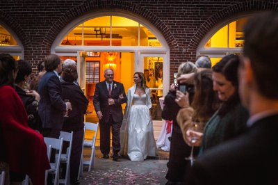 A father guides his daughter down the aisle in the courtyard