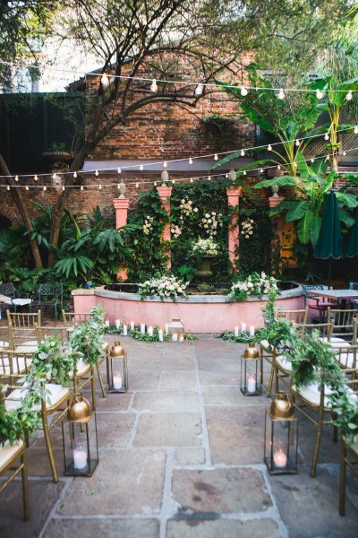 Floral arrangements and candles line the aisle